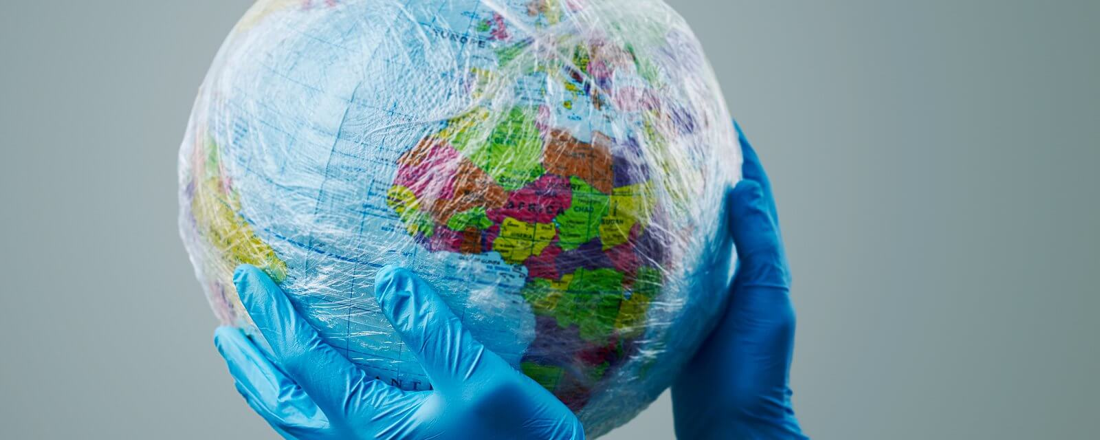 a doctor wearing blue surgical gloves holding a world globe wrapped in plastic, depicting the plastic contamination or the protection against the epidemic infectious diseases or the air pollution