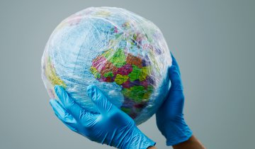 a doctor man wearing blue surgical gloves holding a world globe wrapped in plastic, depicting the plastic contamination or the protection against the epidemic infectious diseases or the air pollution